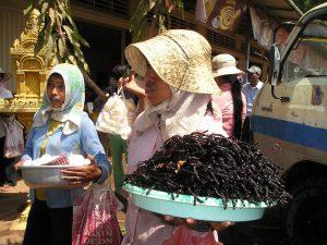 Een meisje loopt met een grote hoeveelheid insecten op een schaal op een markt in Cambodja.