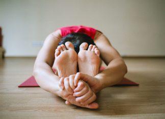 Vrouw in yoga pose op yogamat.