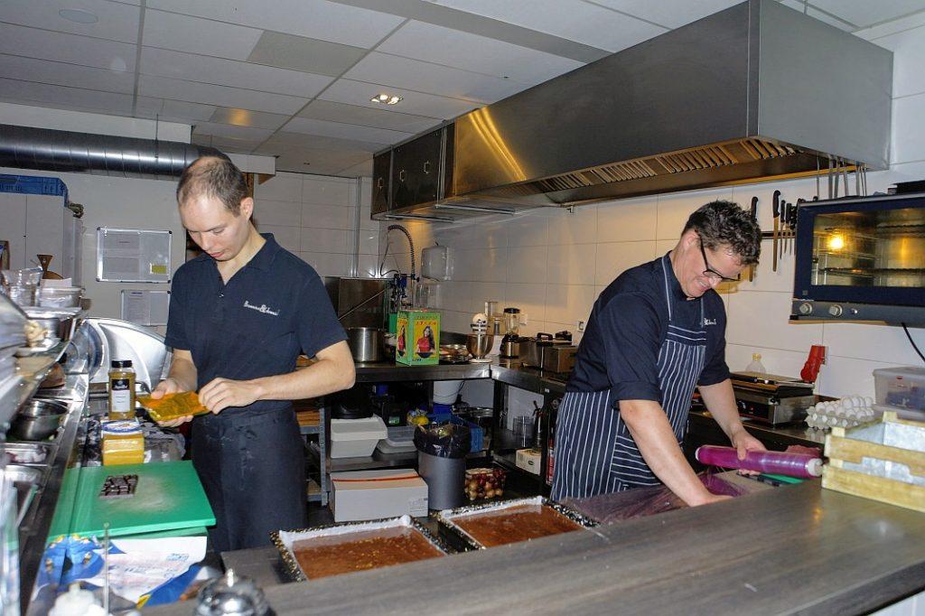 Mark (links) en kok Bram van Erp aan de slag in de keuken. Twee platen brownies staan klaar om de oven in te gaan. Foto: Tonny van Oosten