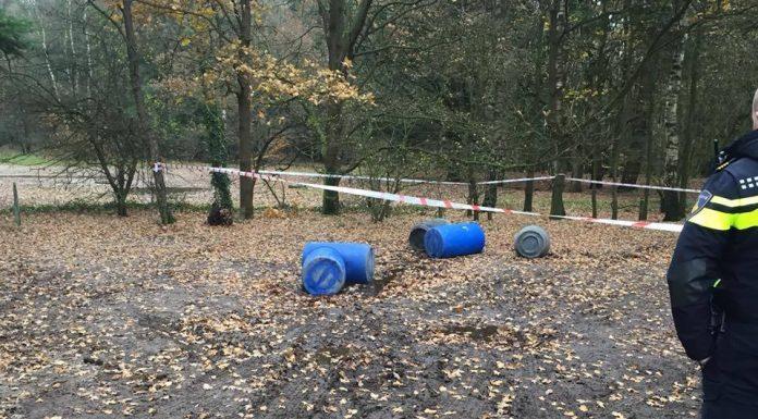 Politieagent kijkt naar gedumpte vaten in het bos bij Wageningen.