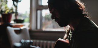 Man speelt gitaar in een huiskamer.