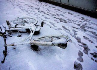 Fiets op de grond in de sneeuw in Wageningen.